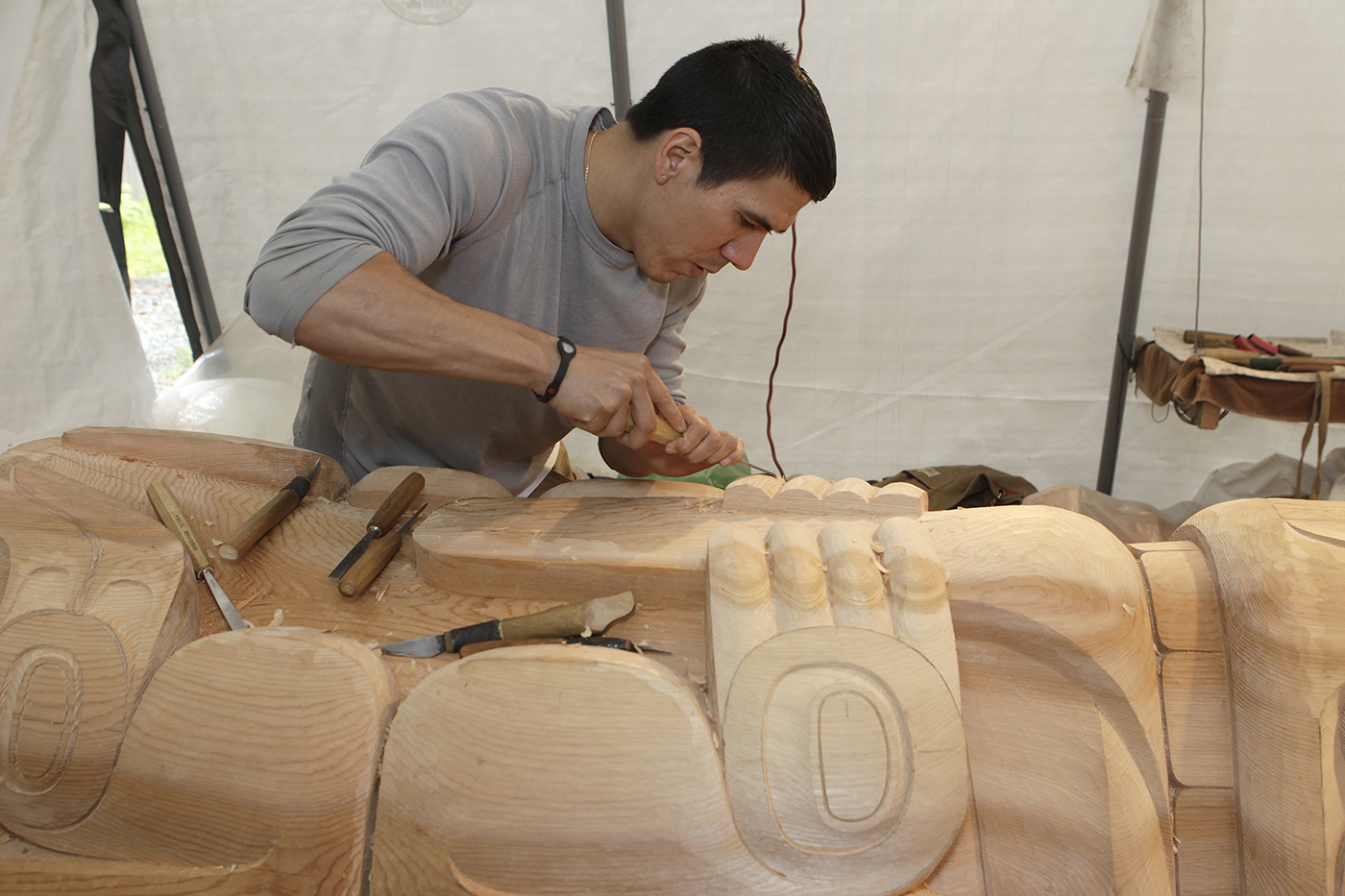 TJ Young working on a totem pole now installed at Gajaa Hít in Juneau